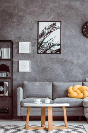 Het schilderen van bladeren op donkere muur boven grijze sofa met geel hoofdkussen in eenvoudige woonkamer