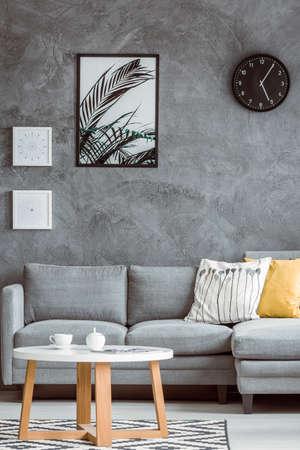 Eenvoudige woonkamer met posters en zwarte klok op concrete muur boven grijze bank met geel hoofdkussen