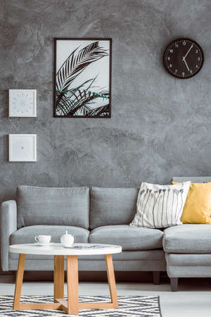 Simple living room with posters and black clock on concrete wall above grey sofa with yellow pillow