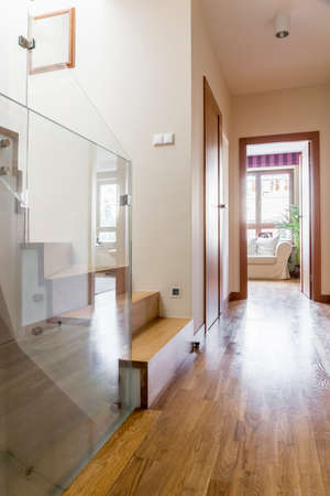 Corridor with glass panel in contemporary apartment with wooden floor
