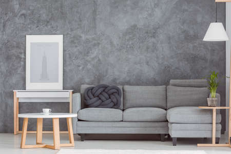 Simple poster on wooden shelf next to grey couch set with black knot pillow in dark living room Stok Fotoğraf