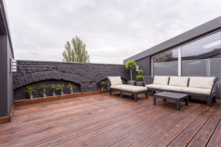 Plants and beige garden furniture on terrace with wooden floor and black brick wall Stockfoto