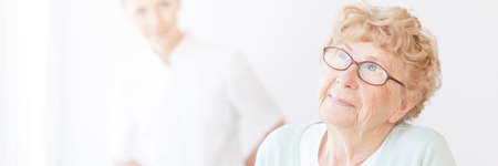 Elderly blonde haired woman looking ahead with hope while being watched over by her young nurse Stock Photo