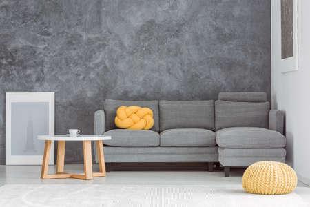 Gelber Puff vor grauem Sofa gegen Betonmauer im Wohnzimmer mit entworfenem Couchtisch Standard-Bild - 84779272