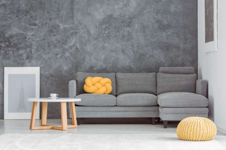 Yellow pouf in front of grey sofa against concrete wall in living room with designed coffee table
