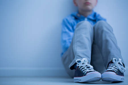 Sad boy in sneakers with aspergers syndrome sits alone in his room Stock Photo