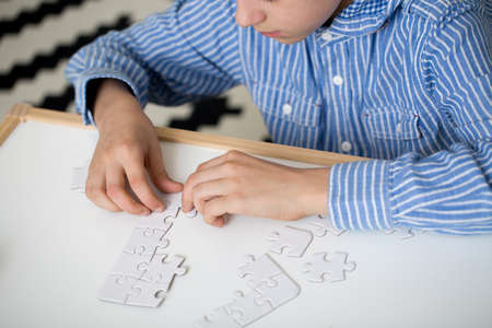 Boy in striped shirt is doing puzzles on white desk at home. Autistic child therapy concept Stock Photo