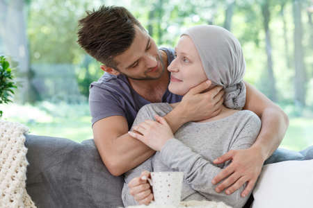 Sick girlfriend in headscarf after radiotherapy supported by loving boyfriend Stock Photo - 84817058
