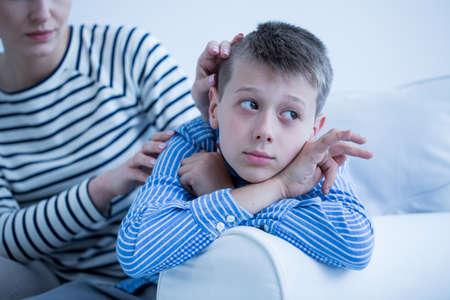 ストライプのシャツで母は白いソファの上に横たわる彼女の自閉症の子供が心配