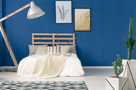 Comfy bedroom with wooden frame, navy blue walls, light bedding Фото со стока - 84817063