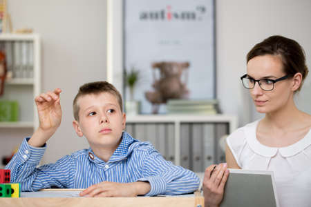 Teacher with notebook observes boy in striped blue shirt solving task. Autistic child therapy concept Stock Photo