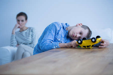 Sad boy sick of autism plays with yellow toy car while his mother is looking at him