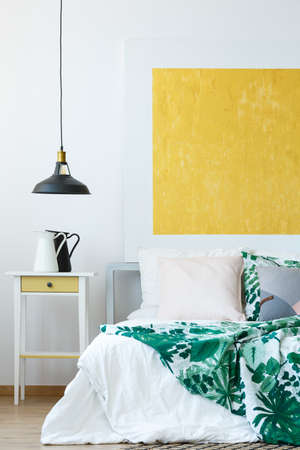 bedside: Pendant lamp, tropical bedclothes and yellow abstract wall decor Stock Photo