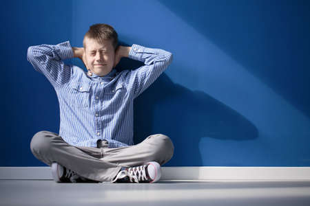 Boy with hypersensitive auditory is covering ears while siting on floor in empty room Stock Photo