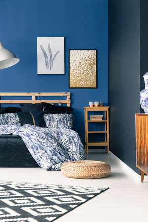 Sophisticated bedroom with elegant blue walls, carpet, pouf and posters
