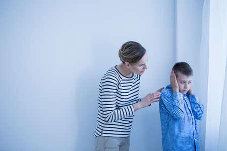 De jongen in blauw overhemd wil niet horen terwijl zijn moeder in gestreept overhemd aan hem spreekt Stockfoto