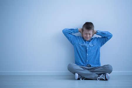 자폐아는 청색 벽이있는 방에 홀로 앉아있는 동안 소리가 나면서 좌절감을 느낍니다. 스톡 콘텐츠 - 84823999