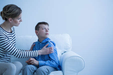 Mom in striped shirt calms her son who has panic attack while sitting on white sofa Stock Photo