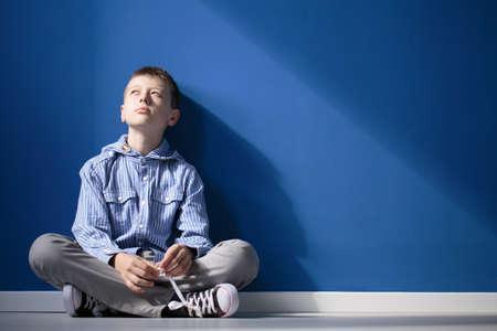 사려 깊은 자폐증 소년 파란색 벽에 흰색 바닥에 교차 다리 앉는 다.