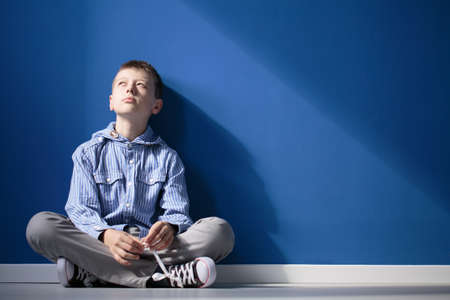 Thoughtful autistic boy sits with crossed legs on white floor against blue wall Imagens - 84823600