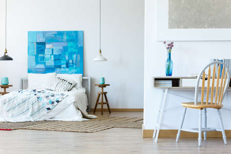 Blue and white bedroom with office area and abstract painting Banco de Imagens