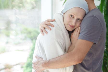 성공적인 화학 요법 후 암을 가진 희망찬 여성을 포옹하는 사랑하는 남편 스톡 콘텐츠