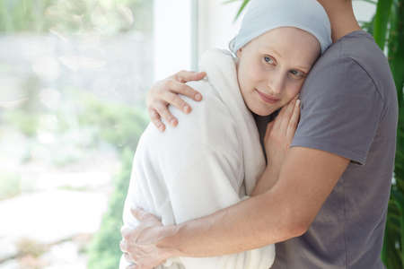 Loving husband hugging hopeful woman with cancer after successful chemotherapy Stock Photo