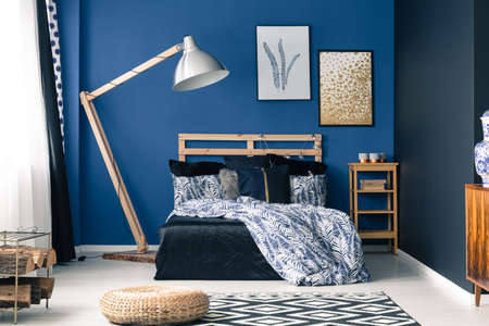 Relaxing bedroom interior in rich blue color with wooden furniture