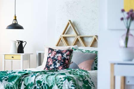 Veelkleurige slaapkamer met tafel, industriële lamp, handgemaakte kussens, driehoekenplanken