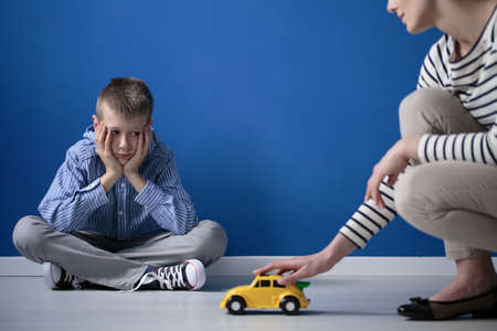Kid is looking on yellow toy car while sitting with crossed legs on white floor Stock Photo