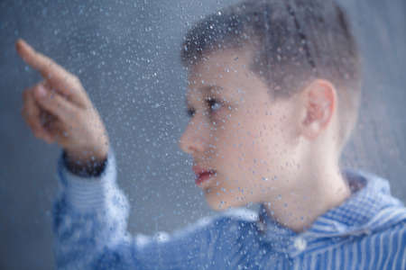 Autistic child in blue shirt is looking on drops of water on window in home Stock Photo