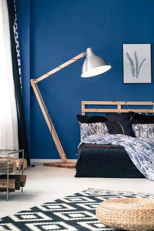 Bedroom with wooden and metal lamp, blue walls and indigo satin bedsheets