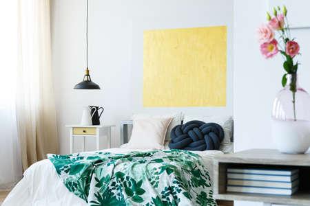 緑の熱帯寝具と黄色のアートワークでゲスト用ベッドルーム