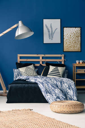 Elegant dark blue bedroom with wooden furniture and wicker pouf