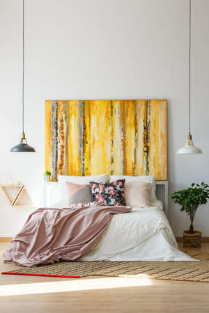 Contemporary yellow artwork in sophisticated bedroom with pastel color scheme Stock Photo - 84823616