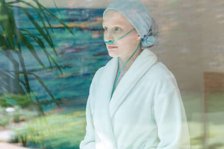 Sick woman in headscarf and nasal cannula looking through window Stock Photo