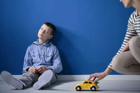 Thoughtful child is looking at window while his mother tries to play with him with yellow toy