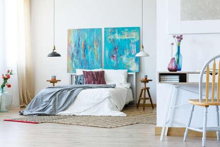 Interior de dormitorio con cama king-size, flores y pinturas multicolores abstractas. Foto de archivo - 84824075