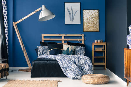 Royal blue bedroom interior with a touch of gold 写真素材