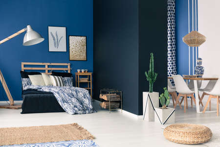 Functional soothing navy blue apartment with bed and dining space