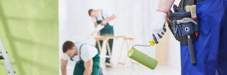 Man met groene verf roller en gereedschap, timmerman in de achtergrond