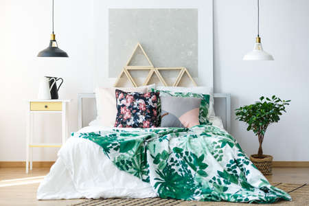 Natural colored bedroom with delicate furniture and botanical prints Stok Fotoğraf