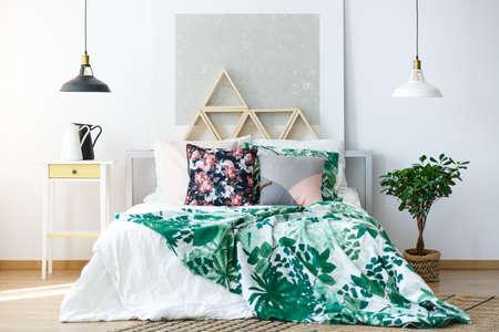 Natuurlijk gekleurde slaapkamer met delicate meubels en botanische prints Stockfoto