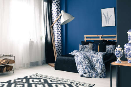 Calming blue bedroom with wooden bed frame and cobalt wall Stock Photo