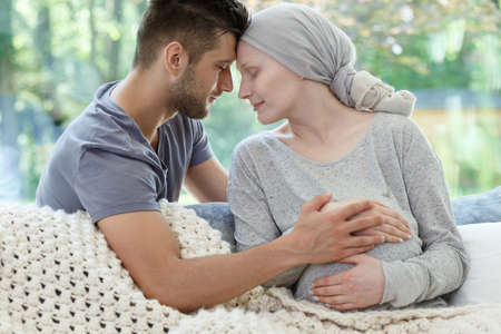 Loving supporting husband and his pregnant wife suffering from cancer Stock Photo