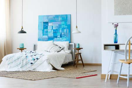 Camera da letto elegante con pittura blu contemporanea e biancheria da letto modellata Archivio Fotografico - 84817182