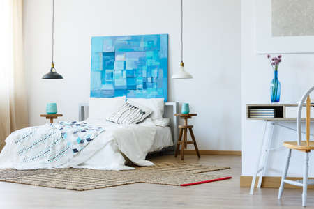 Stylish bedroom with contemporary blue painting and patterned bedclothes