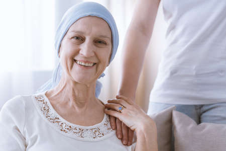 Mentally strong smiling woman suffering from cancer holding daughters hand