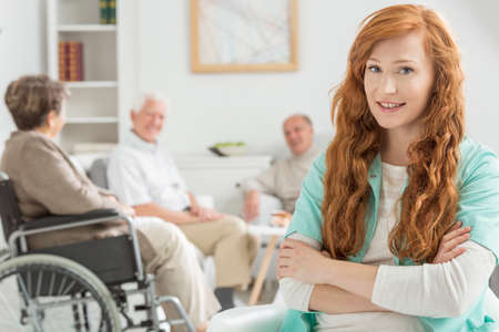 Young nurse watch over elderly people in bright common room
