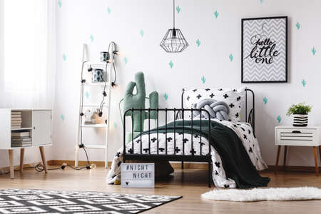 Toy in shape of cactus next to bed with black blanket and grey braided pillow in kids room with painting